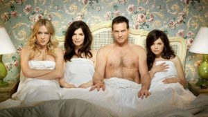 two couples in bed together