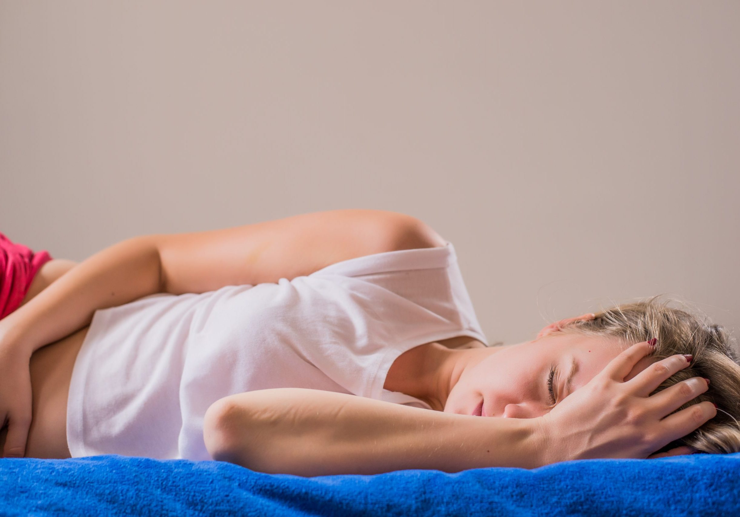 woman in pain lying on bed
