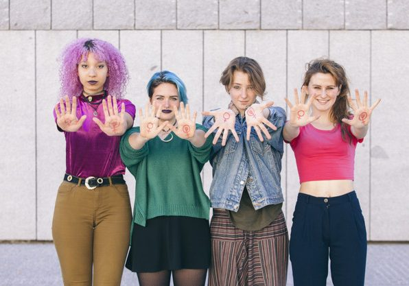 group of young and diversity women with the symbol of feminism written oh their hands and showing them to the front